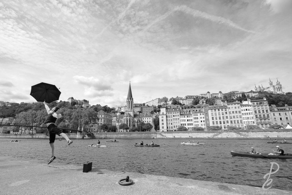 artiste de mime Lucas Petracci en train de sauter avec un parapluie vue sur Fourvière choisir entre photo noir et blanc ou photo couleur